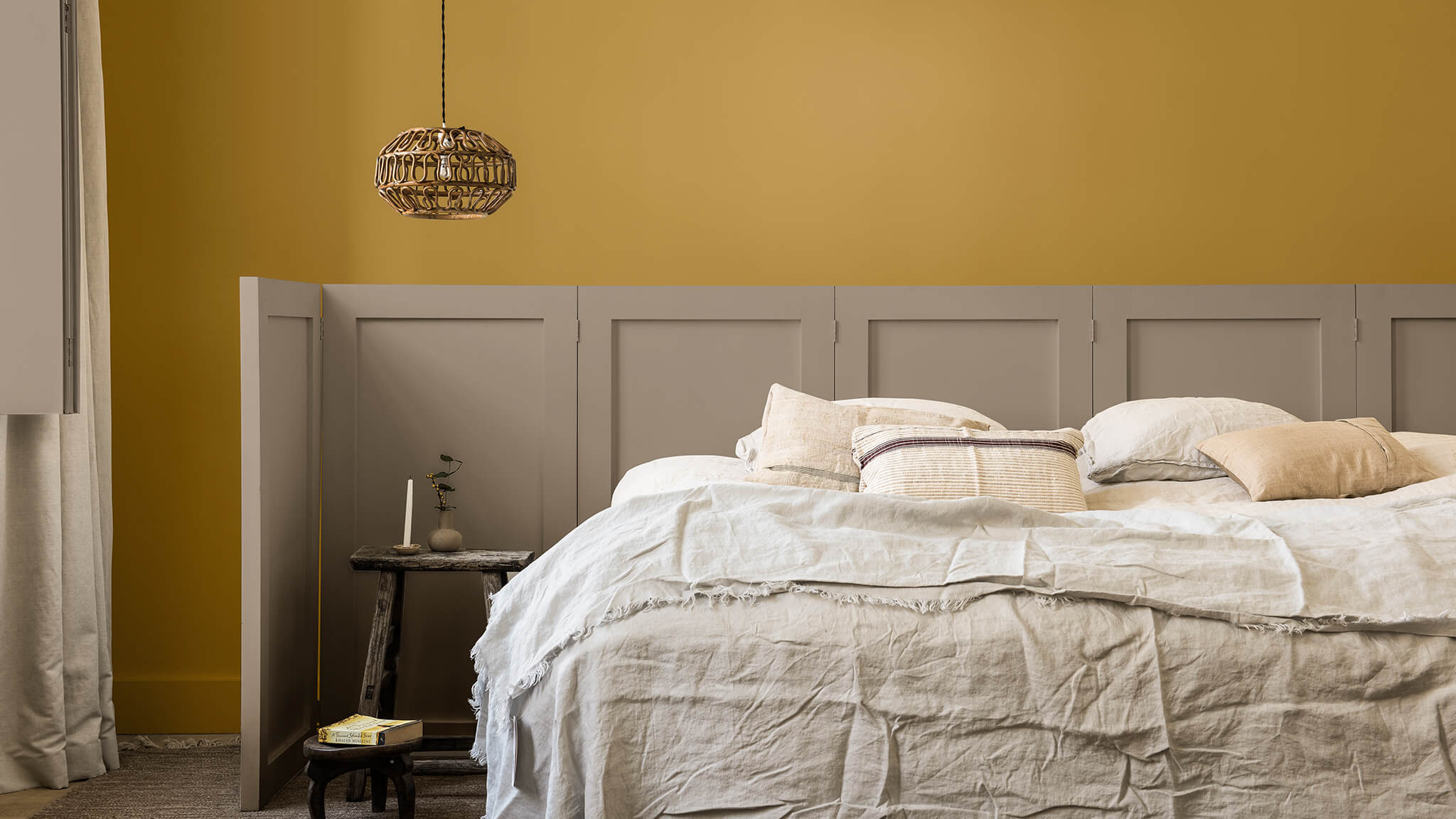 Slaapkamermuur geverfd in goudgeel en Brave Ground™, met lambrisering achter het bed