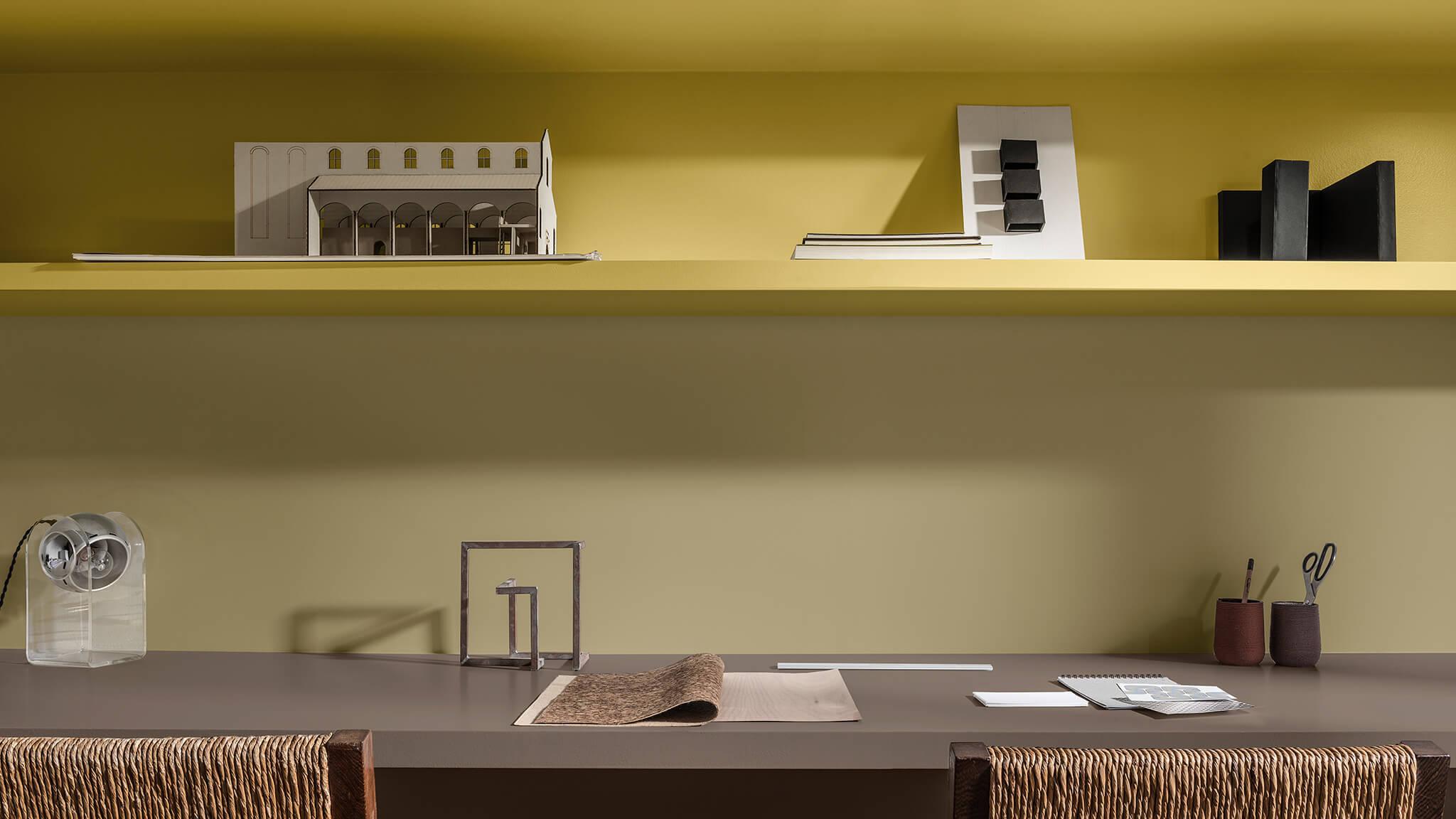 Planken in de werkkamer in geel en Brave Ground™, plus twee gevlochten stoelen.